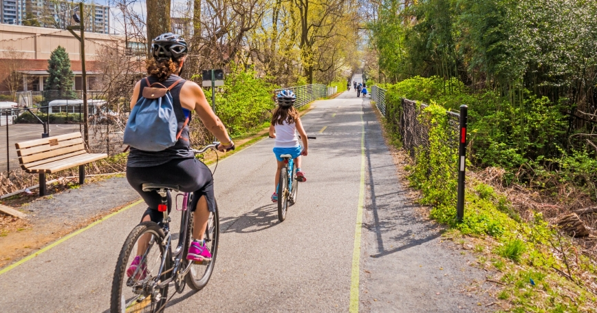 A mother and daugher ride on an urban bike path