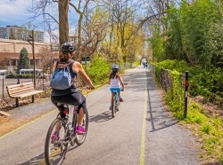 A mother and daughter ride on an urban bike path