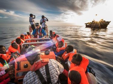 Refugees, who were rescued in international waters off the Libyan coast, are transferred from one boat to another, December 2016