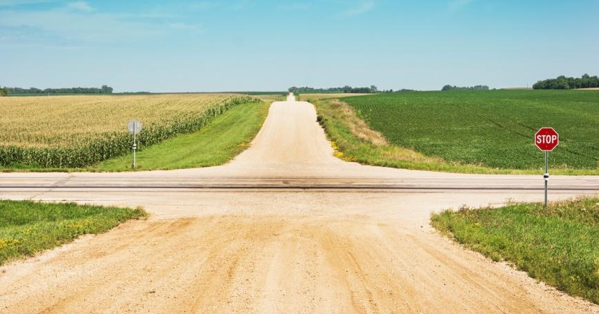 An intersection of gravel roads through a field