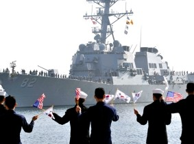 The USS Lassen arrives at a South Korean naval port in Donghae as sailors wave South Korean and U.S. flags, March 9, 2013