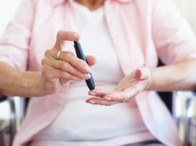 A senior woman in a wheelchair checking her blood sugar level with a device