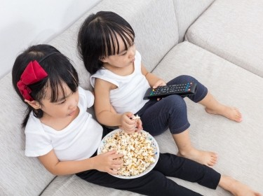 Two girls on a couch watching TV while eating popcorn