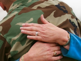 A woman hugging her soldier son or grandson