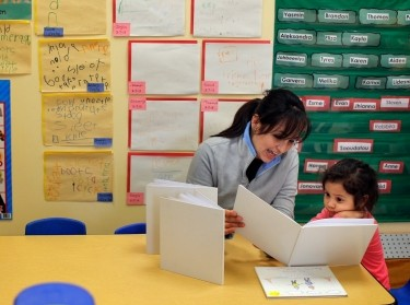 A mother reads with her three-year-old daughter at a Head Start program in Boston, Massachusetts, March 5, 2013