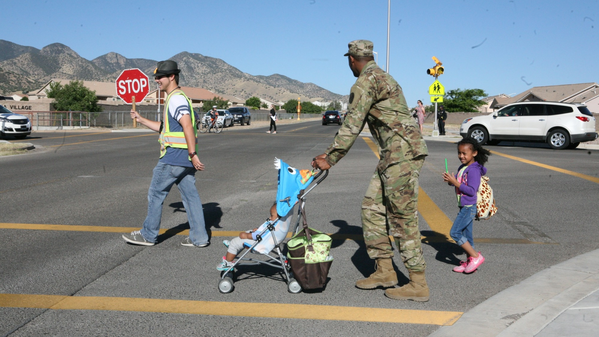An officer walking his children to school and daycare on Bike and Walk to School and Work Day at Fort Huachuca, Arizona, May 4, 2016