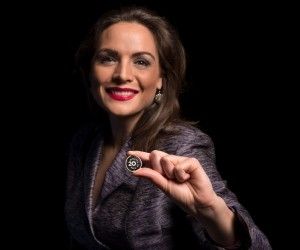 Kathryn Bouskill, a social scientist at RAND, holds a coin worth 20 minutes of time, photo by Diane Baldwin/RAND Corporation