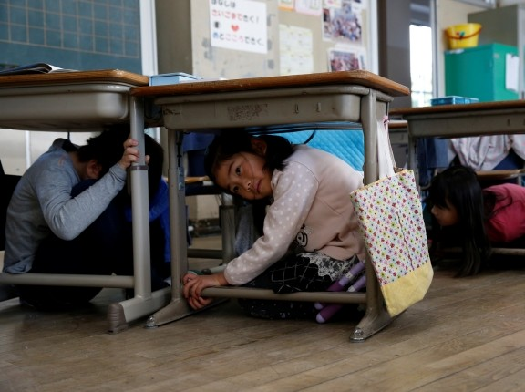Children take shelter under desks during an earthquake simulation in an evacuation drill in Tokyo, Japan, March 10, 2017, photo by Issei Kato/Reuters