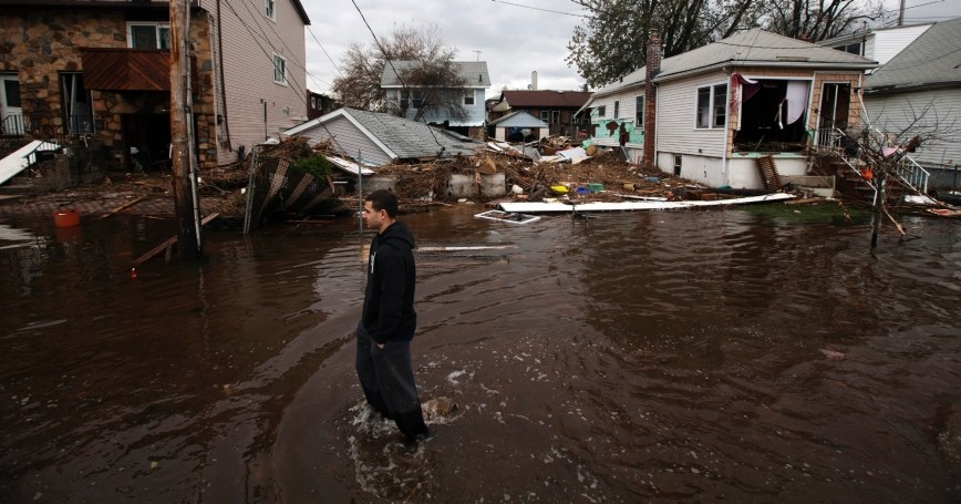 A man walks through floodwaters to survey damage from Hurricane Sandy in the New Dorp Beach neighborhood of Staten Island, New York, November 1, 2012, photo by Lucas Jackson/Reuters