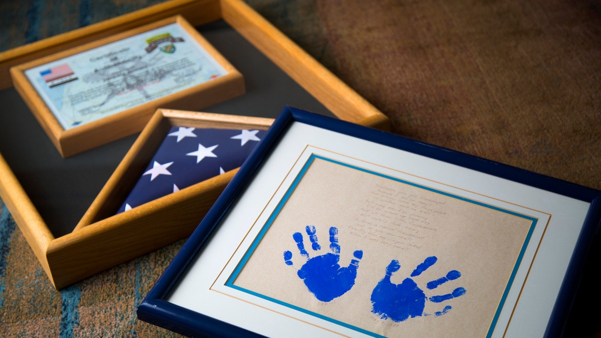 A framed U.S. flag and framed handprints, photo by Howard Lipin/San Diego Union-Tribune via Zuma Wire