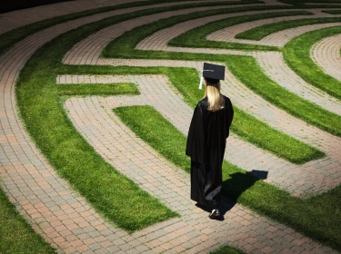 A woman wearing a graduation cap and gown entering a maze, photo by YinYang/Getty Images