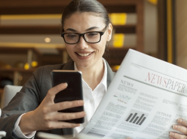 A woman holding a newspaper and a cell phone, photo by izzetugutmen/Adobe Stock