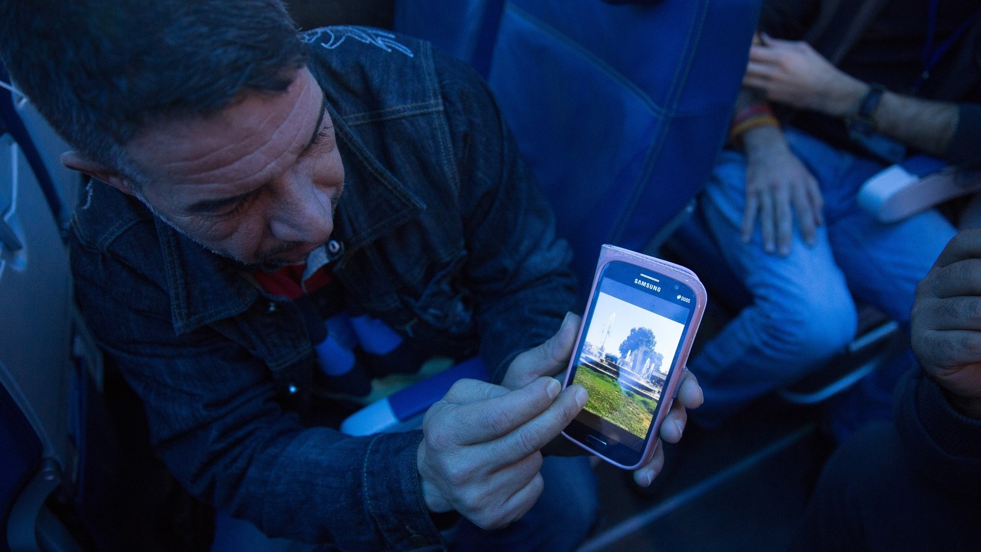 A Syrian refugee shows his hometown of Hama on his phone while en route to Canada, photo by IOM/Muse Mohammed 2015/CC BY-NC-ND 2.0