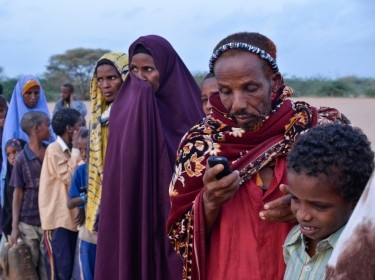 A man texts on his mobile phone while waiting in line at dawn to register at Ifo refugee camp in Dadaab, Kenya, photo by Internews Europe/Flickr CC BY-NC-ND 2.0