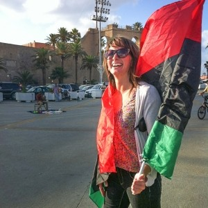 Erica Kaster with a Libyan flag in the main square of Benghazi, Libya, 2011, photo courtesy of Erica Kaster