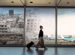 Woman walking through airport with luggage and an image of bombed Syrian city superimposed on the background, photos by Drazen_/Getty Images and fly_and_dive/Adobe Stock