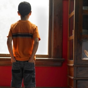 A boy looking out a window with his hands in his pockets, photo by Ryan McVay/Getty Images