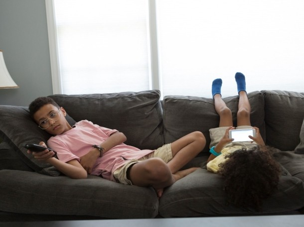 Two children on a couch watching TV and their phones, photo by patrickheagney/Getty Images