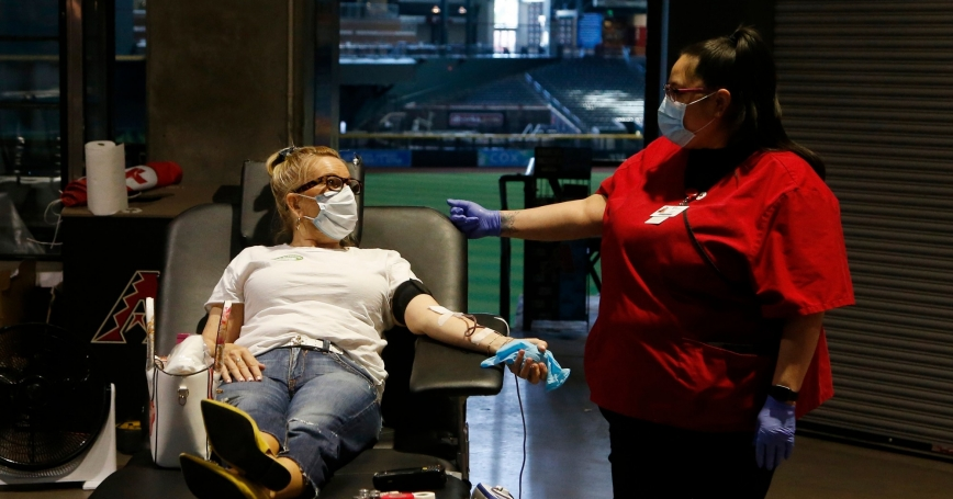 A person donates blood during a Red Cross and Arizona Diamondbacks baseball team blood drive at Chase Field in Phoenix, April 28, 2020, photo by Ross D. Franklin/AP Images