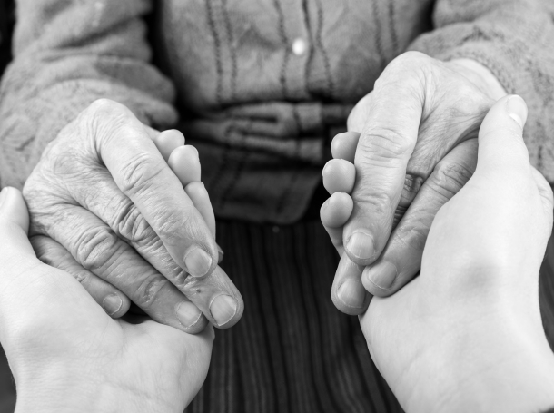 Closeup of two peoples' hands holding each other, photo by Obencem/Getty Images