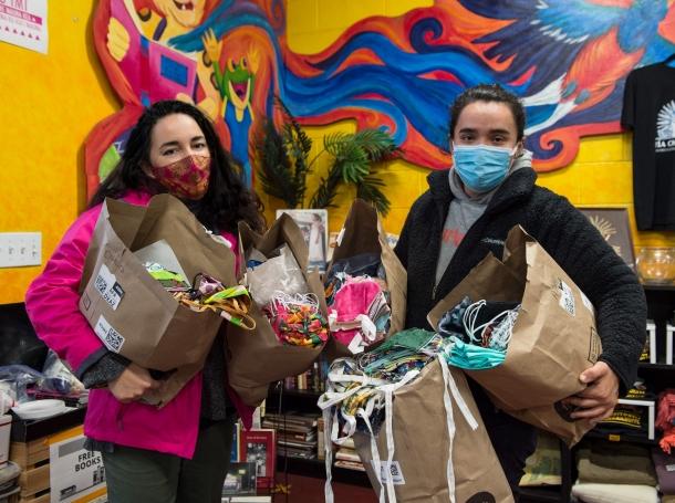 Jessica Arana (left) delivering over 1,400 handmade masks to Tia Chucha's cultural center in Sylmar, California, photo by Diane Baldwin/RAND Corporation