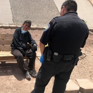Gallup Police Officer J. Soseeah checks on the health of a woman in Gallup, New Mexico, photo by Morgan Lee/AP Images