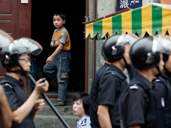 An ethnic Uyghur boy stands at the door of his home as Chinese security forces secure the area in Urumqi, China, July 10, 2009, photo by Nir Elias/Reuters