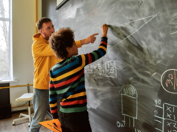 Science teacher explaining rules and formulas in physics and mechanics to a student at a blackboard, photo by LanaStock/Getty Images