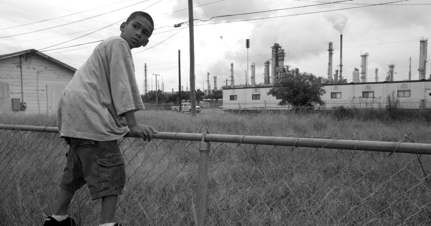 A boy in the Hillcrest section of Corpus Christi, Texas, at the fence line of a refinery in August 2007, photo by Peter Essick/Cavan Images/Alamy