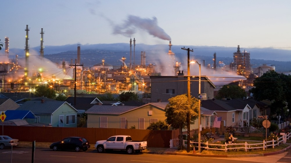 Homes abut an oil refinery near the Port of Los Angeles at Long Beach, photo by Peter Bennett/Alamy
