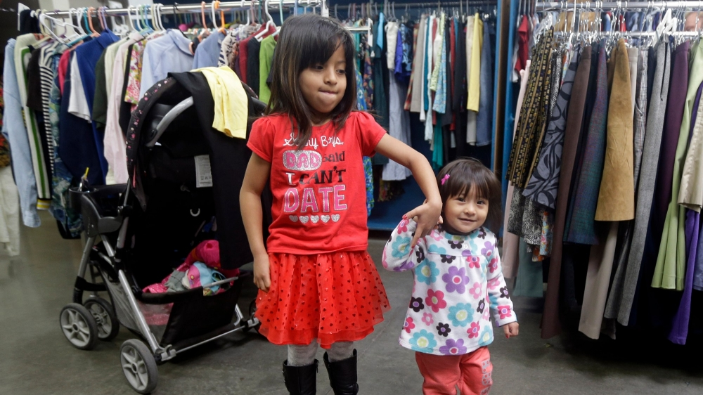 In Silicon Valley, home to some of the highest incomes in the U.S., girls wait for their mother at a used clothing giveaway, photo by Marcio Jose Sanchez/AP Images