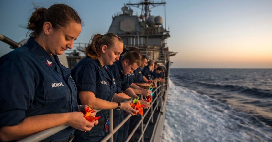 Sailors aboard the USS San Jacinto pray for suicide victims during a suicide prevention and awareness event called Walk Out of Darkness