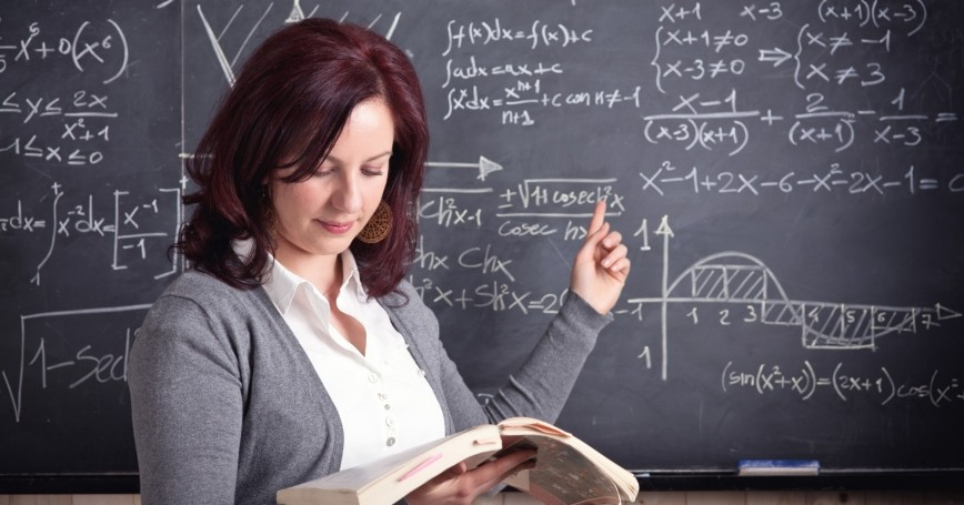 Math teacher pointing at blackboard of equations