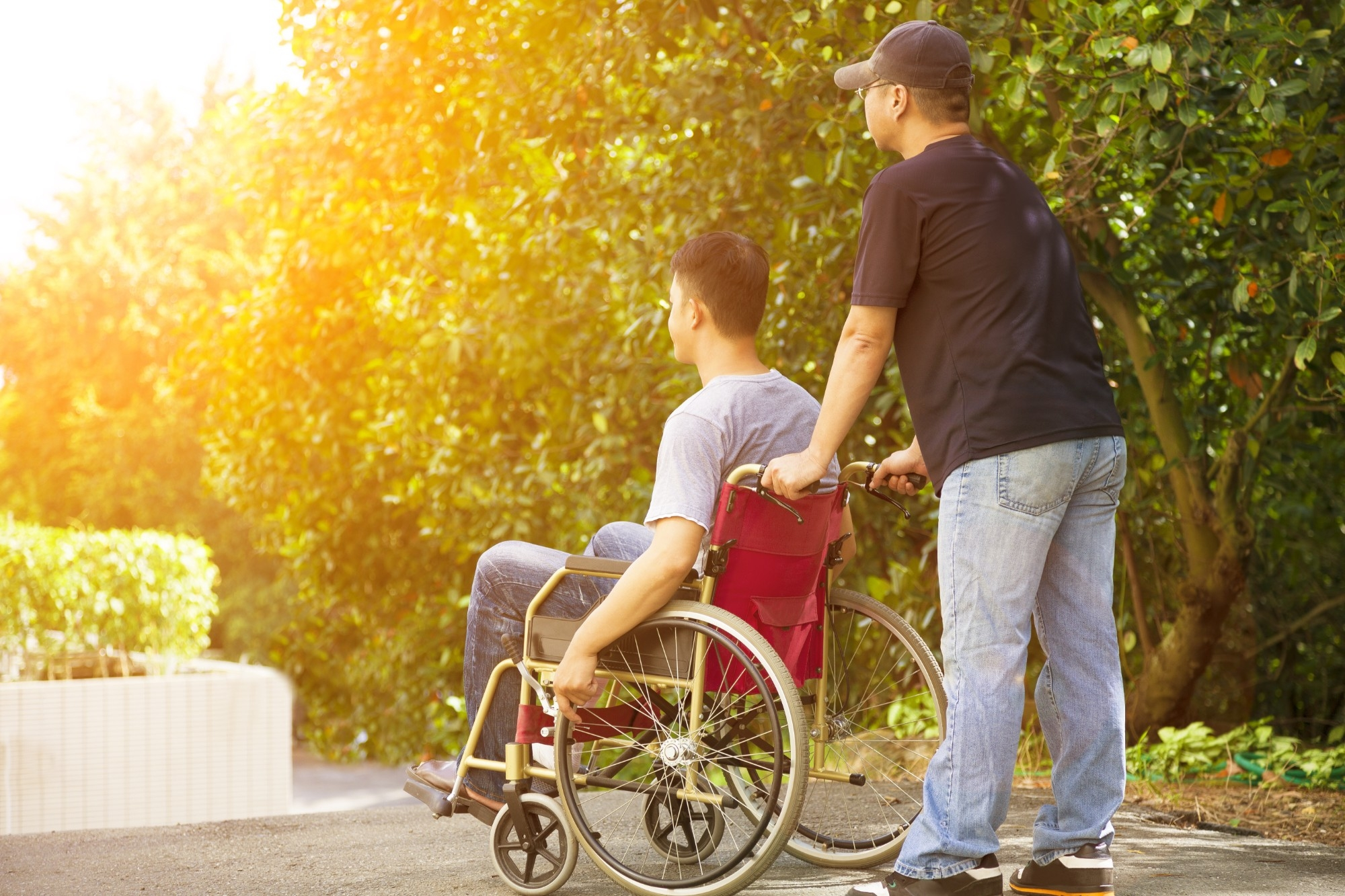 Young man sitting in a wheelchair with caregiver