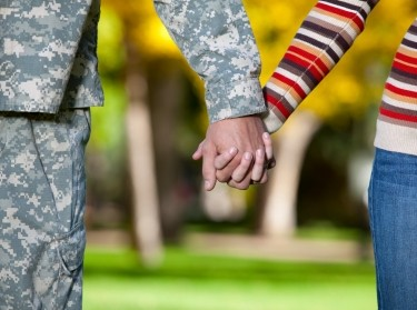A servicemember and his wife hold hands