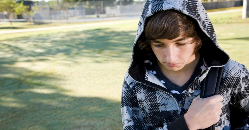 Depressed boy carrying a backpack
