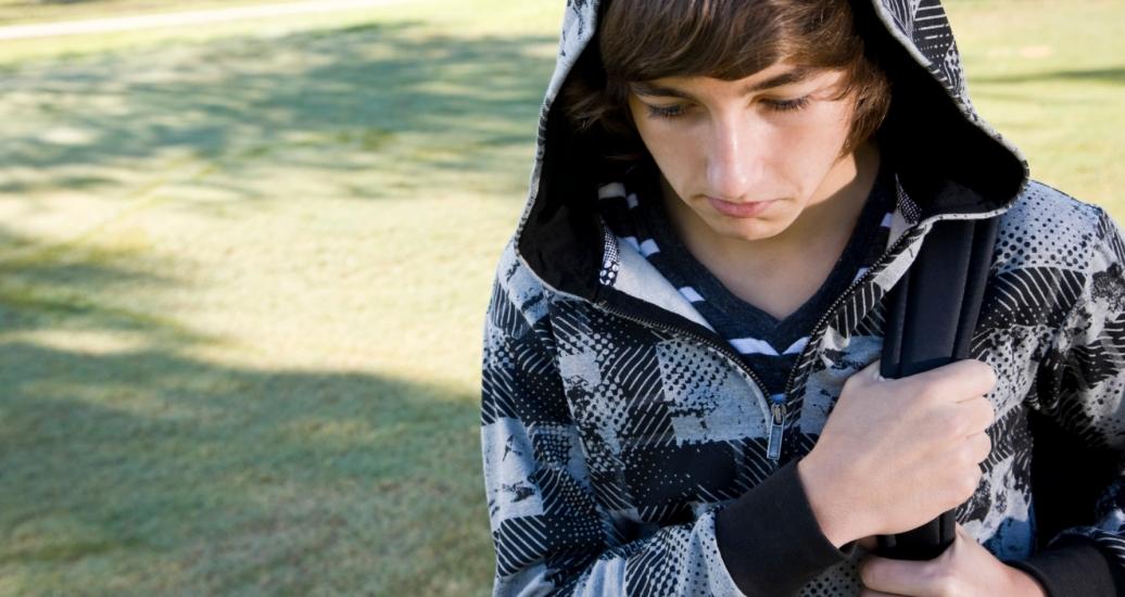 depressed teen boy carrying backpack