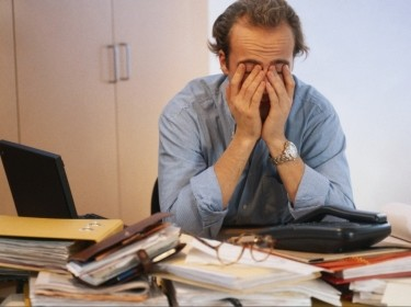 A man stressed in his office covering his eyes
