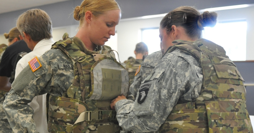 A soldier gets help adjusting her protoype Generation III Improved Outer Tactical Vest at Fort Campbell, Kentucky