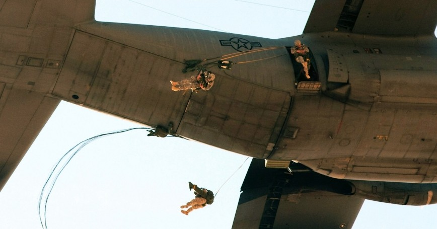 Paratroopers exit a C-130 aircraft at Al Asad Airbase, Iraq, as part of an airborne training exercise