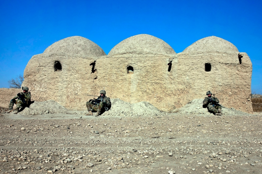 U.S. Army soldiers lean against a mud wall during a break from combat operations in Kandahar province, Afghanistan, January 9, 2012