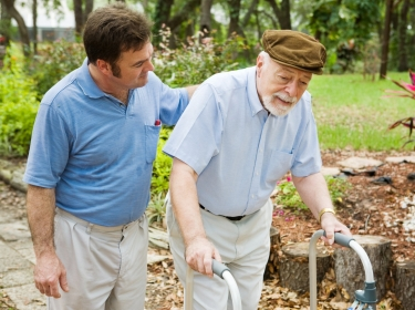 A younger man helping an elderly man who is using a walker