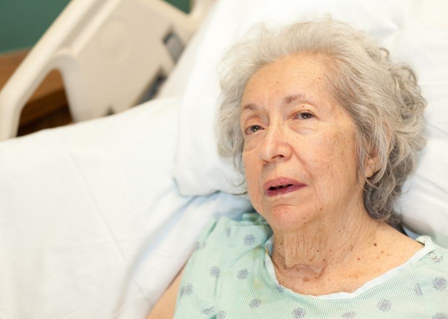 An elderly woman in a hospital bed