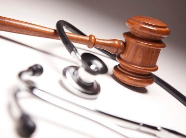 Gavel and stethoscope on gradated background