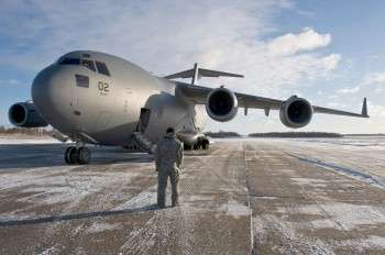 U.S. Air Force Tech. Sergeant flying crew chief from Papa, Hungary communicates with the C-17 Globemaster III pilots on an airfield in Lithuania, December 10, 2010