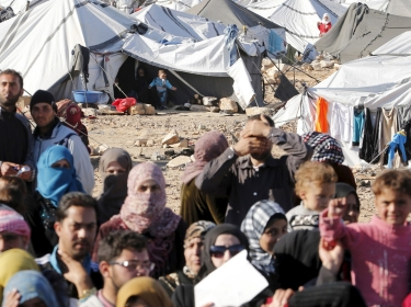 Syrian refugees, stuck between the Jordanian and Syrian borders, wait to cross into Jordan near the town of Ruwaished, January 14, 2016