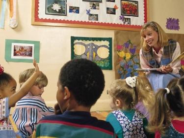 Preschool or kindergarten student raising her hand as teacher reads a book