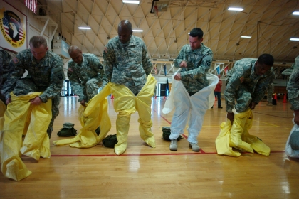 U.S. Army soldiers, earmarked for the fight against Ebola, put on protective suits during training before their deployment to West Africa.