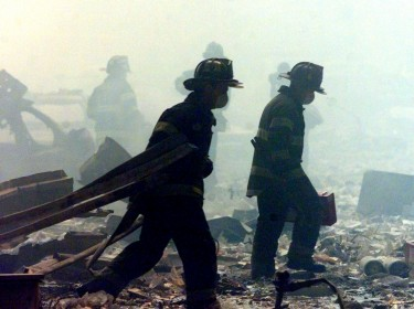 A group of firefighters walk amid rubble near the base of the destroyed World Trade Center in New York on September 11, 2001
