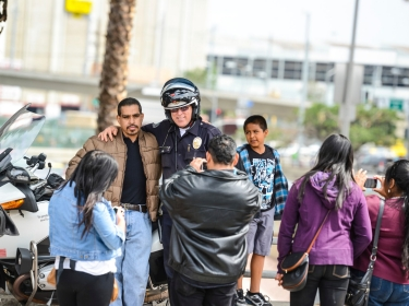 A policeman and a citizen pose together at a Cinco De Mayo Celebration in Los Angeles, CA
